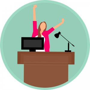 graphic-of-woman-with-arms-in-air-excited-for-weekend-while-at-her-work-desk-with-computer-and-lamp