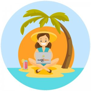 caribmedia-aruba-emoji-woman-with-laptop-smiling-while-sitting-under-palmtree-sunset-is-seen-along-with-water-surrounding-the-sand-she-sits-on-and-theres-an-aruba-ariba-drink-next-her